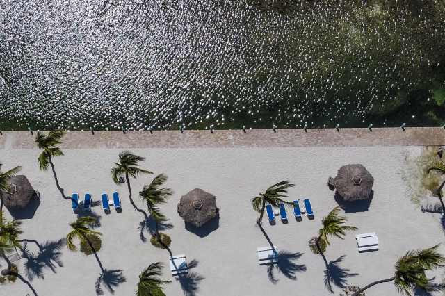 An aerial view shows a deserted beach resort in Windley Key, some 70 miles south of Miami, on March 22, 2020, during the coronavirus outbreak. The Florida Keys have closed down to visitors. Heavily relying on tourism, at the peak of high season, Florida's most southern holiday islands have been forced to shut down hotels amid the COVID-19 pandemic.