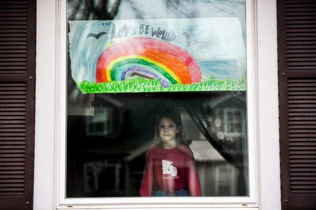 Kate Madsen, 6, displays her drawing in her window in hopes that it would cheer her neighbors up on March 25, 2020 in Sioux Falls, S.D. Madsen and her first-grade classmates are learning remotely to prevent the spread of the coronavirus at Robert Frost Elementary School. The 6-year-old says she misses her teachers, friends and art class.