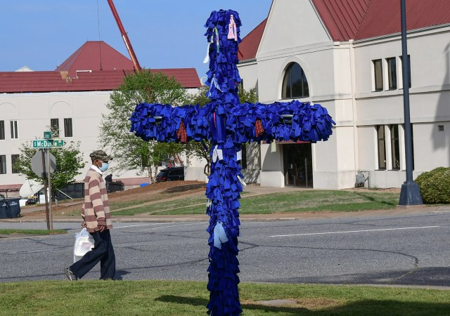 A man wearing a mask walks by St. John's United Methodist Church COVID-19 Cross of Hope in Anderson, S.C. on April 9, 2020. The cross with royal blue ribbons for each diagnosed person in South Carolina started when there were 450 cases, but as the cross was placed in front of the church Thursday morning, the cases in South Carolina are at 2,552 with 63 deaths.
