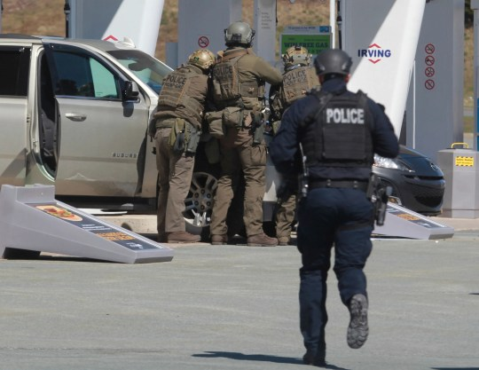 The Royal Canadian Mounted Police confront a suspect at a gas station in Enfield, Nova Scotia, on April 19. A gunman disguised as a policeman shot people in their home and set fire to a rampage in the Canadian province. Officials said on Sunday that the alleged shooter had died.