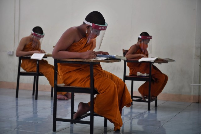 Novice monks wearing face shields as a preventive measure against the spread of the COVID-19 coronavirus attend religious studies at Wat Molilokkayaram Buddhist temple in Bangkok, Thailand on April 20, 2020.