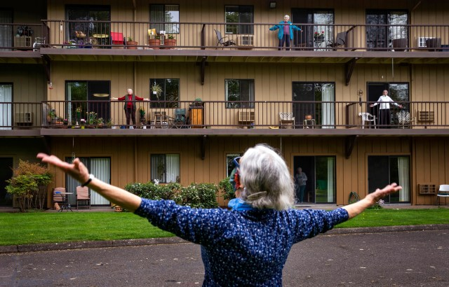 Fitness coordinator Janet Hollander, leads a session of Balcony Boogie from outside Willamette Oaks in Eugene, Oregon for residents sheltering in their apartments during the COVID-19 shutdown Tuesday April 21, 2020. The staff of the senior housing center have modified some of the regular routines for residents, staging activities like morning stretches and aerobic opportunities while still observing social distancing protocols.