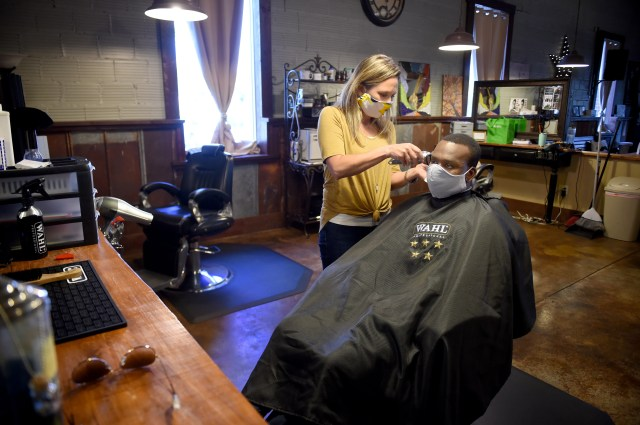 Shelley Craft, owner of The Men's Refinery BarberSpa gives a haircut to Kenneth Gregory at her salon in Augusta, Ga., Friday morning April 23, 2020.