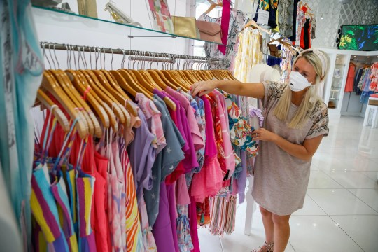 Emilee Young of Austin Lorin, a store in Colleyville, Texas, is organizing tops when the store reopens on April 24.