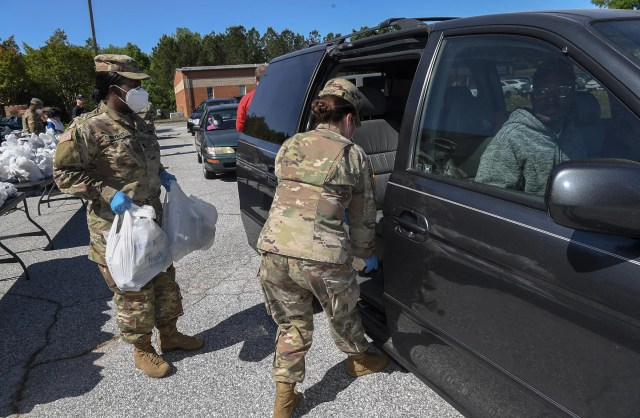 Tymber Bryant, left, and Jackie Baker, with the 228 Theater Tactical Signal Brigade of the South Carolina National Guard in Spartanburg, place food in the car of Sterling Crawford of Abbeville, food from Second Harvest Food Bank of Metrolina at the Department of Social Services Abbeville County Government Buildings in Abbeville, S.C. on Friday, May 1, 2020. Donal Dickens, the Williamston Branch Manager of Second Harvest Food Bank of Metrolina said there was enough food for three days for 500 families who drove through, which ran out in two hours.