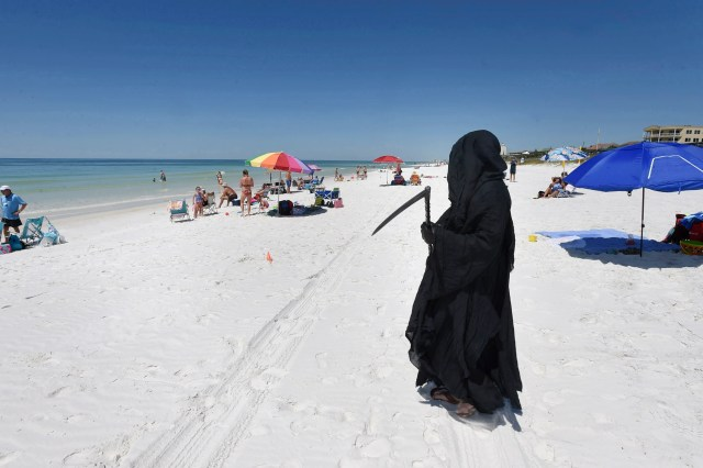 """Dressed as the Grim Reaper, Florida Attorney Daniel Uhlfelder talks with reporters after walking the newly opened beach near Destin, Fla on Friday, May 1, 2020. Uhlfelder was protesting the Walton County (Florida) Commission's decision to reopen the county's beaches in spite of the COVID-19 pandemic. """"In these circumstances, I can see no rational reason to open our beaches, effectively inviting tens of thousands of tourists back into our community"""" Uhlfelder said in a news release. """"If by dressing up as the 'Grim Reaper' and walking our beaches I can make people think and potentially help save a life – that is the right thing to do."""""""