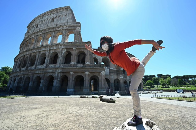 A woman holds a yoga posture as she exercises by the Colosseum monument in Rome on May 4, 2020, as Italy starts to ease its lockdown, during the country's lockdown aimed at curbing the spread of the COVID-19 infection, caused by the novel coronavirus. Stir-crazy Italians will be free to stroll and visit relatives for the first time in nine weeks on May 4, 2020 as Europe's hardest-hit country eases back the world's longest nationwide coronavirus lockdown.