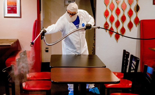 Joe Barnes, owner of Safe Spray Services, sprays disinfectant at Rococo restaurant as he treats and cleans the surfaces on Friday, May 15, 2020, in Oklahoma City, Okla. Barnes turned his grease traps cleaning service to a COVID-19 deep-cleaning service, that includes disinfectant spay, clean-up and UV ray treatment, to contribute to the pandemic response and keep his employees paid.