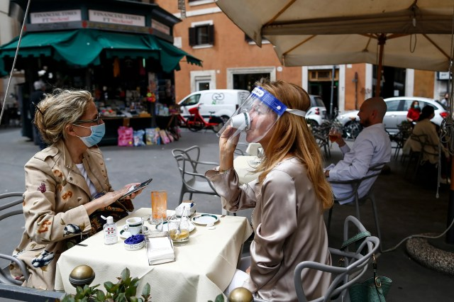 A woman sips her coffee from under her facial protection at a cafe with outdoor tables in Rome, May 18, 2020. Italy is slowly lifting restrictions after a two-month coronavirus lockdown.
