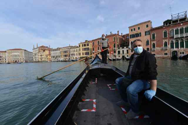 A gondolier wearing a face mask transports his very first customer as service resumes at the San Toma embankment on a Venice canal on May 18, 2020 during the country's lockdown aimed at curbing the spread of the COVID-19 infection, caused by the novel coronavirus.
