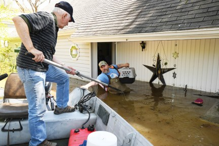 Don Thomas of Saginaw pulls his boat up to his son Jason Thomas who went back to his flooded house near W. Signet in Midland to retrieve his family's two cats.