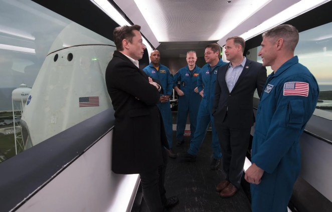 SpaceX CEO Elon Musk, left, speaks with NASA Administrator Jim Bridenstine and astronauts Victor Glover, Doug Hurley, Robert Behnken and Mike Hopkins. The group met at pad 39A's crew access arm March 1, 2019, as it was connected to Crew Dragon.
