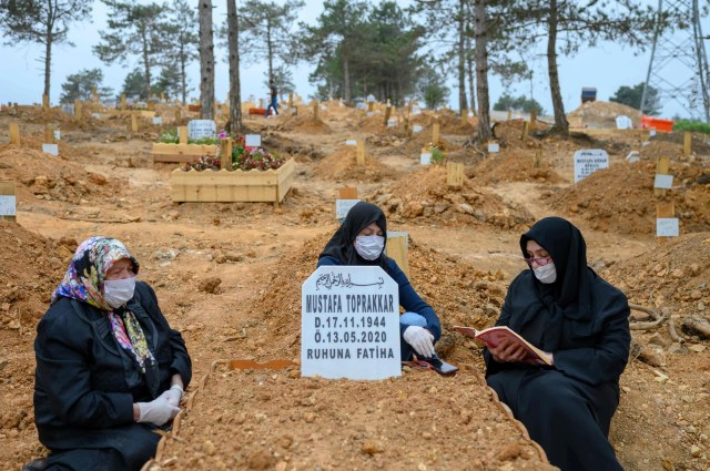 Women wearing protective face masks pray at a cemetery at the grave of a relative who died of COVID-19, on May 21, 2020, in Istanbul, amid the COVID-19 outbreak caused by the novel coronavirus. The cemetery in the city's Beykoz district on the Asian side was built in March when Turkey confirmed its first case. Now it houses more than 700 people who died of contagious diseases including COVID-19.