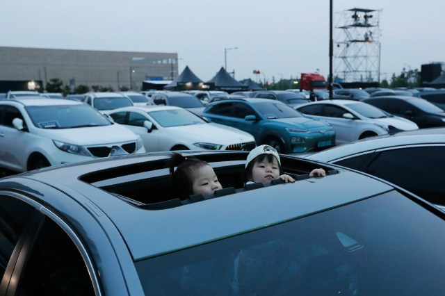 Young children look out of the sun roof of a car ahead of the Stage X drive-in concert at KINTEX parking lot in Goyang, South Korea, Saturday, May 23, 2020. The concert's aim is to provide entertainment for South Korean citizens who have been craving for music events that have been suspended during the coronavirus outbreak.