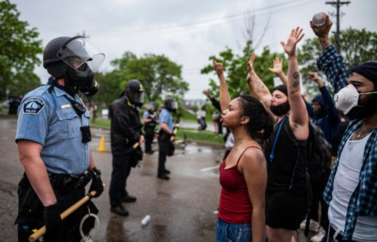 Protesters and police face each other during a rally for George Floyd in Minneapolis.