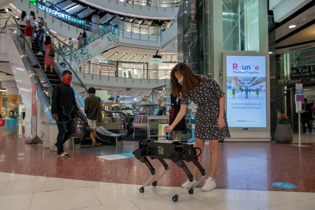 A woman disinfects her hands from a mobile robot that carries a container of sanitization liquid at Central World, an upmarket shopping mall in Bangkok, Thailand, Wednesday, May 27, 2020. Thai government continues to ease restrictions related to running business in capital Bangkok that were imposed weeks ago to combat the spread of COVID-19.