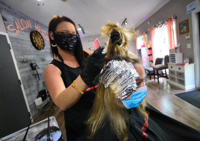 Kalea Shippee, owner of Salon Meraki, in Brattleboro, Vt., works on dying the hair of Jen Delano on Friday, May 29, 2020. Friday was the first time the salon was allowed to open up since Vermont closed all hair salons and barbershops because of the COVID-19 pandemic.