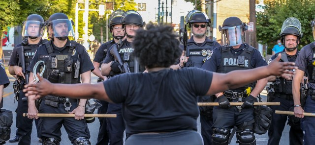 A crowd gathers in Louisville, Kentucky, on May 30, 2020, to protest the killing of Breonna Taylor. Police in riot gear block them from moving down the road.