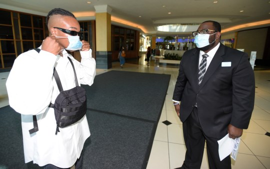Shopper Nahson Kellum, left, of Southfield, puts on a face mask that is offered by mall concierge Eddie Cooper as he enter the Somerset Collection.