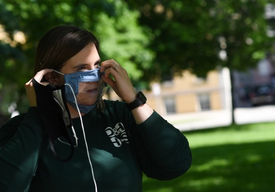 Jessica Oliver of Deaf and Hard of Hearing Services puts on a clear-paneled mask on Thursday, June 4, 2020, at Reutter Park in downtown Lansing. The mask helps people with hearing impairments read lips.