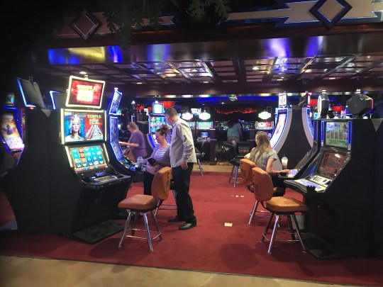 Ryan Sheltra, general manager of Bonanza Casino, assists a customer on reopening day, June 4, 2020, in what was the former table games area of the casino, now converted to slot machines.