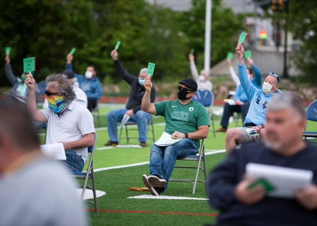 Residents cast their votes during the annual town meeting on June 2, 2020 in Worcester, Mass. The meeting was held on the Auburn High football field to adhere to social distancing guidelines due to COVID-19.