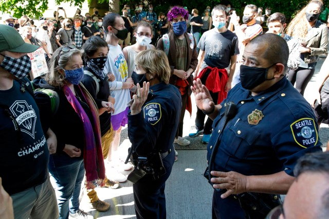 Seattle Police Assistant Chief Deanna Nollette and Assistant Chief Adrian Diaz are blocked by protesters from entering the newly created Capitol Hill Autonomous Zone (CHAZ) in Seattle on June 11, 2020.