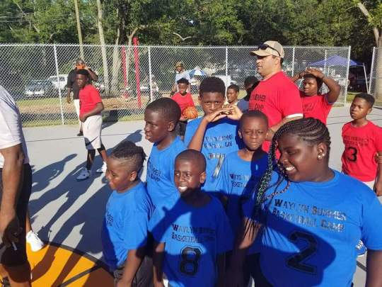 Jesse Williams, in tan cap with sunglasses, coaches city youths in Charleston, South Carolina. Williams, a longtime city activist, is running for county office in order to push for legislative reforms that will improve life for Black residents.
