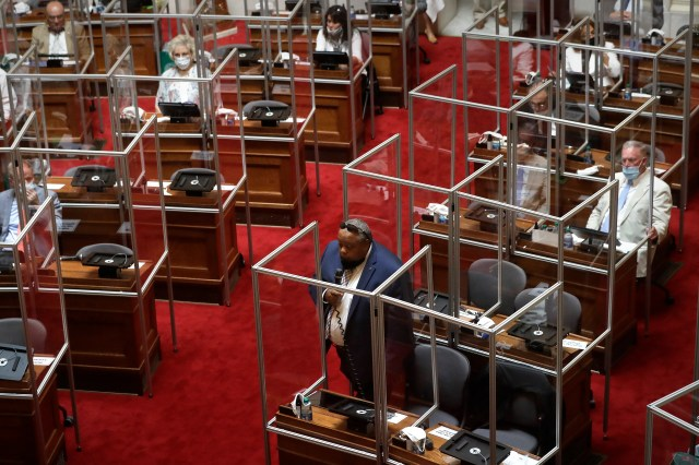 Rhode Island Democratic state Rep. Raymond Hull, below center, holds a microphone on the floor of the House Chamber while separated by plastic protective barriers at the start of a legislative session, Wednesday, June 17, 2020, at the Statehouse, in Providence, R.I. Wednesday's session was the first by the legislature to be held on the floor of the chamber since March of 2020 due to the coronavirus pandemic.