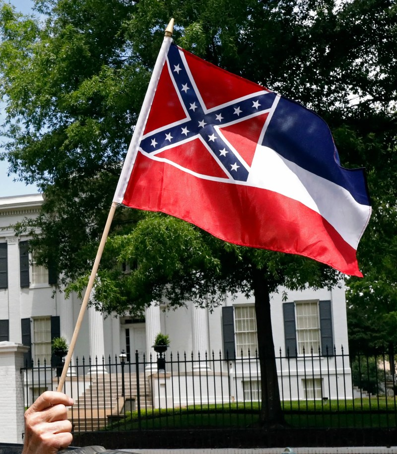"In this file photo a small Mississippi state flag is held by a participant during a drive-by ""re-open Mississippi"" protest past the Governor's Mansion, in the background, in Jackson, Miss."