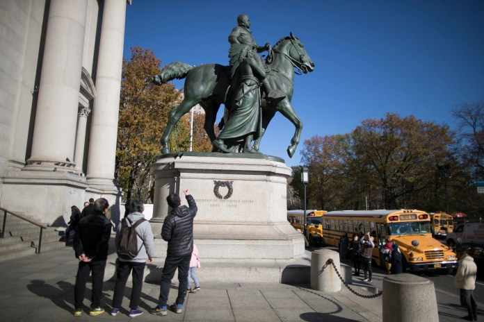 In this Nov. 17, 2017 file photo, visitors to the American Museum of Natural History in New York look at a statue of Theodore Roosevelt, flanked by a Native American man and African American man. The statue will be coming down after the museum's proposal to remove it was approved by the city.