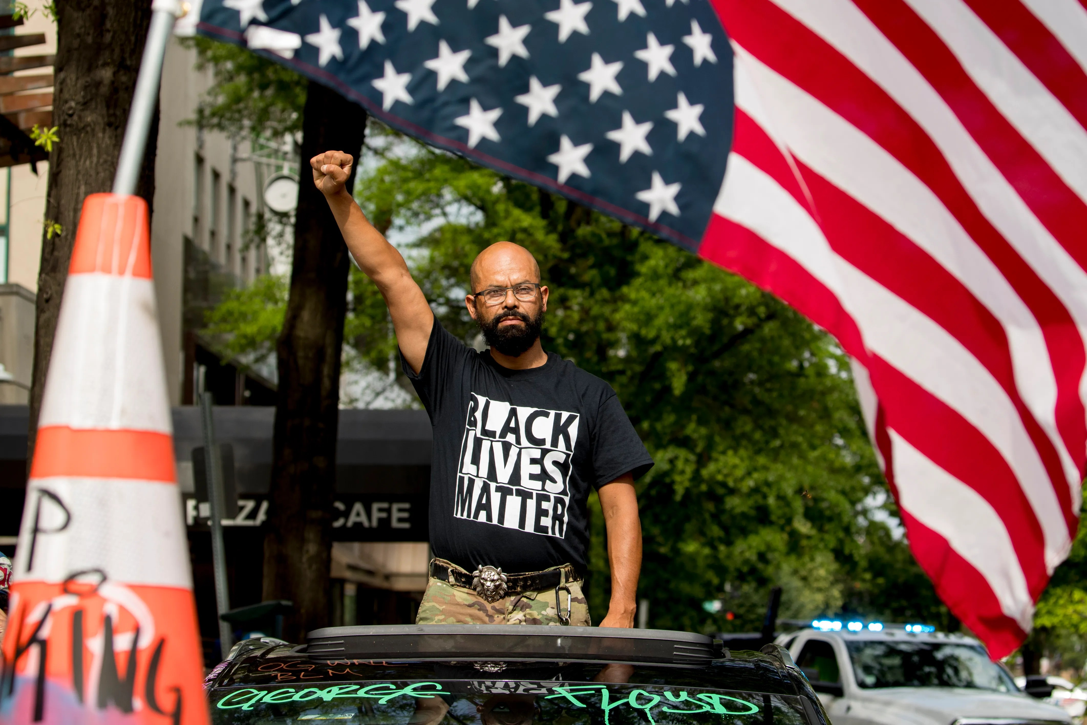 In this June 19, 2020, file photo, George Floyd's name is written on the windshield as John Coy wears a shirt that reads Black Lives Matter and stands through his sunroof with his fist in the air at 16th Street Northwest renamed Black Lives Matter Plaza near the White House in Washington.