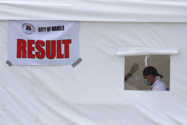 A man wears a face mask inside a tent at a free COVID-19 drive-thru testing facility in Manila, Philippines on Monday, July 20, 2020. Confirmed coronavirus infections in the Philippines soared past 50,000 in early July in a troubling milestone for a country that has reopened an economy on the brink of recession while still struggling to combat the pandemic.