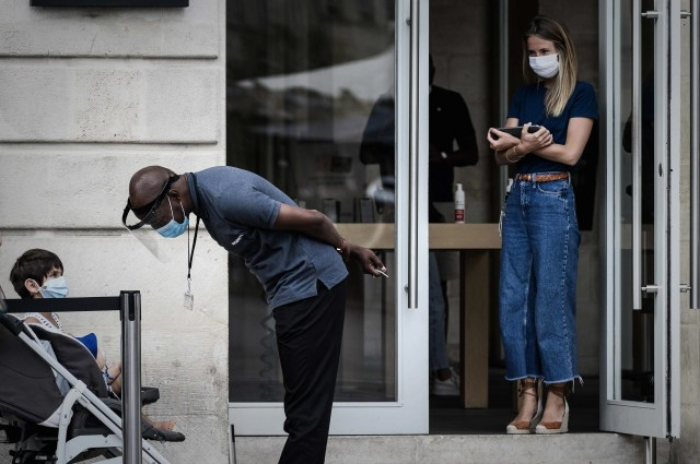 A security personnel with a face shield chats with a kid wearing a protective face mask due to the COVID-19 coronavirus pandemic, outside a shop in Bordeaux, southwestern France, on July 20, 2020.