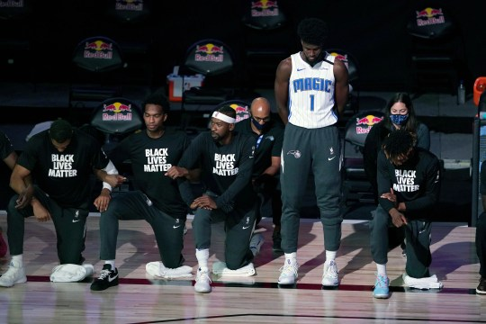 July 31: Magic forward Jonathan Isaac stands as others kneel during the national anthem before playing the Nets.