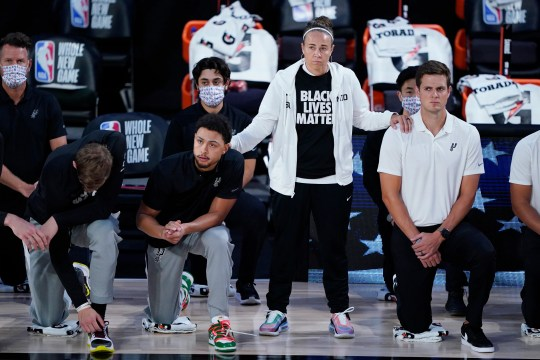 San Antonio Spurs assistant coach Becky Hammon stands beside players as they kneel before a game against the Memphis Grizzlies on Sunday, Aug. 2, 2020, in Lake Buena Vista, Fla.