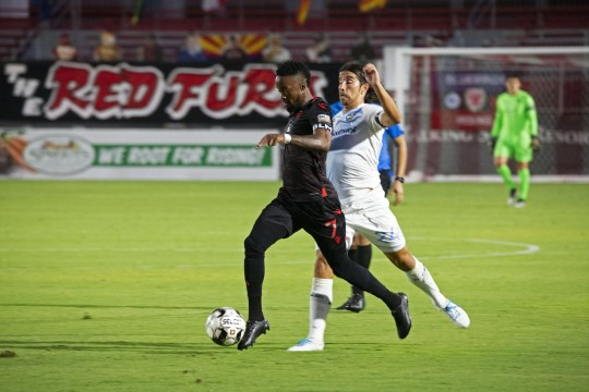 August 1, 2020; Tempe, AZ, USA; Forward Junior Flemmings streaks past El Paso midfielder Yuma to take a strike on net. Flemmings records one goal in the 3-1 victory over El Paso Locomotive. Mandatory Credit: Justin Toumberlin/The Arizona Republic via USA TODAY NETWORK