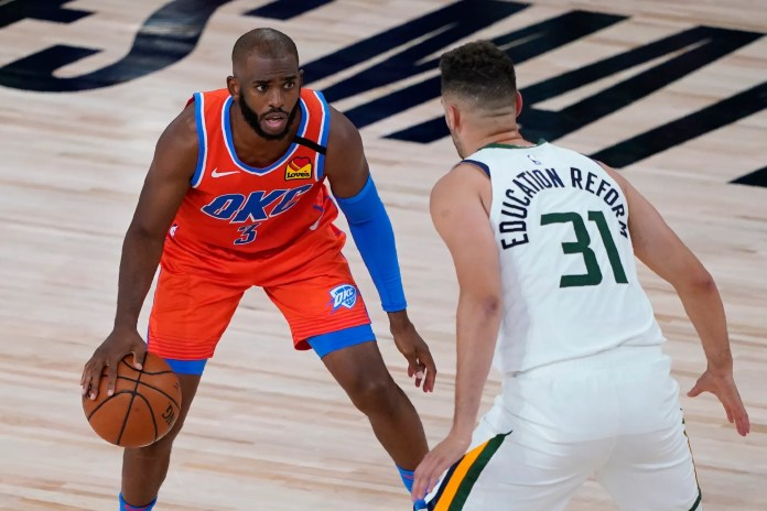 Aug. 1: Thunder guard Chris Paul looks for room to work against Jazz defender Georges Niang.