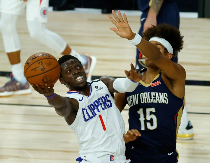 Aug. 1: Clippers guard Reggie Jackson drives to the hoop against Pelicans defender Frank Jackson.