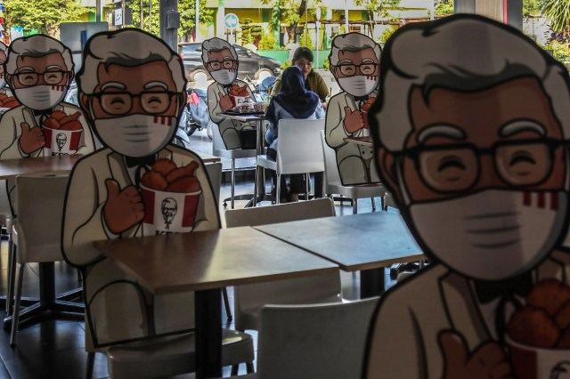 Visitors to a fast-food restaurant share a seat with Colonel Sanders' cutout as an effort to force a physical distancing as a measure to prevent COVID-19 coronavirus spread in Medan, North Sumatra on August 7, 2020.