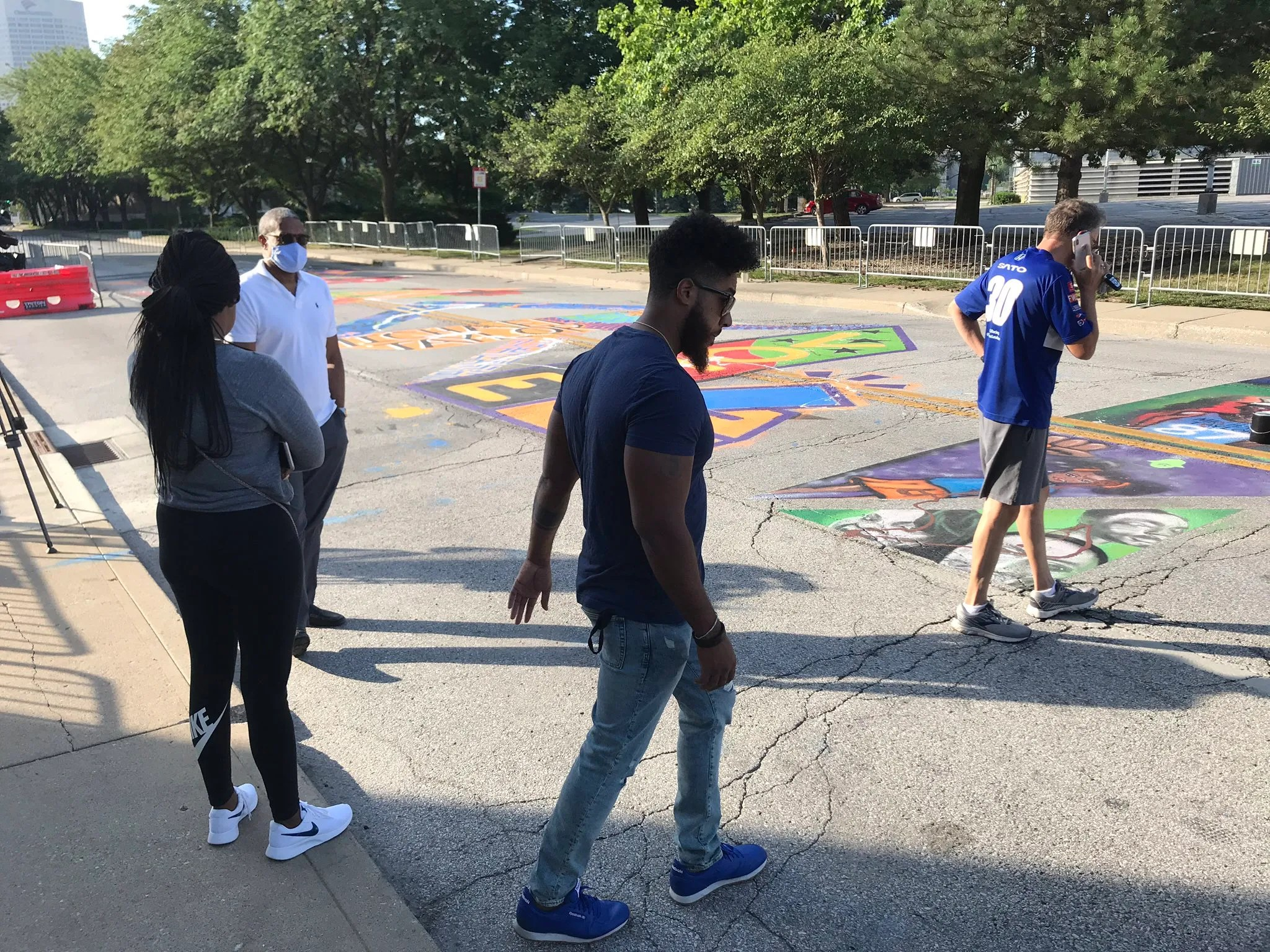 """On-lookers inspect the defaced """"Black Lives Matter"""" mural on Indiana Avenue while trying to call police to the scene to inspect the scene and file a report."""