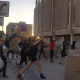 Protesters knock down a barricade to get closer to the Phoenix Police Department Headquarters on August 9, 2020, in Phoenix.