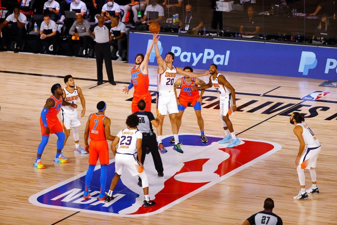 Aug. 10: The Phoenix Suns' Dario Saric, center right, and the Oklahoma City Thunder's Mike Muscala, center left, jump for the opening tip. The Suns won 128-101 to remain undefeated in the bubble.