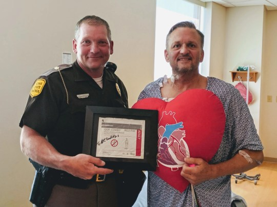 Iowa State Patrol Trooper Bob Conrad visits Greg Abbey at the MercyOne Iowa Heart Center in Des Moines after Abbey suffered a heart attack riding in RAGBRAI July 24, 2019, near Centerville.
