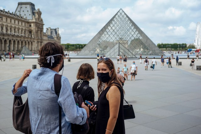 A woman wears a face masks as she poses for a picture at the Louvre Museum in Paris, Saturday, Aug. 15, 2020. Paris extended the areas of the city where pedestrians will be obliged to wear masks starting Saturday morning after health officials said that the coronavirus is