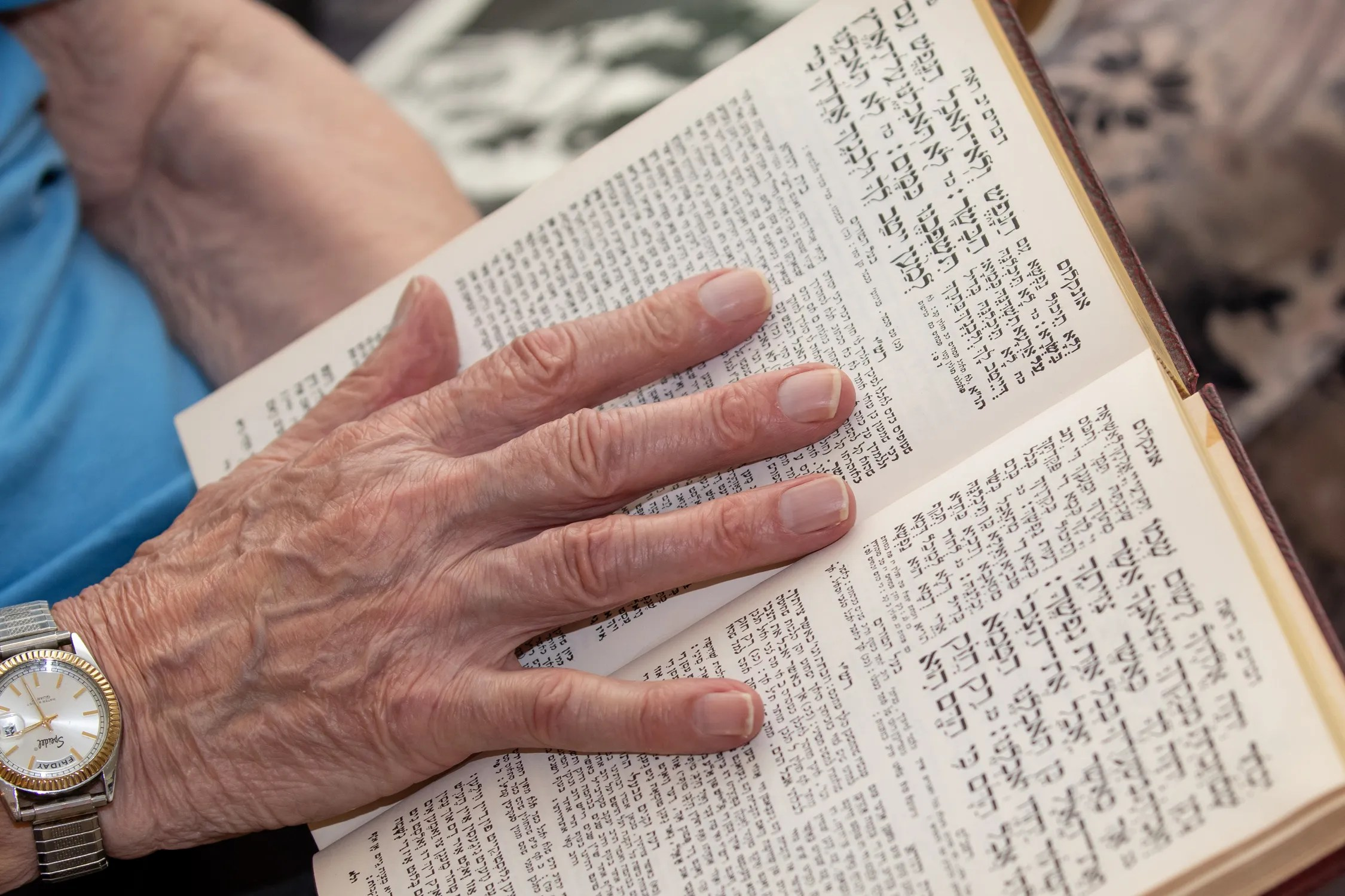 Ernie Gross, a holocaust survivor living in Philadelphia, leafs through the pages of a Siddur prayer book, as he shares his story Friday, July 31, 2020.