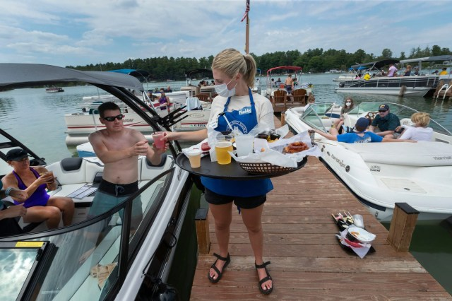 Server Maddie Fink delivers a drink order Aug. 13 at the Clear Water Harbor Restaurant & Bar in Waupaca. Because of the coronavirus pandemic, more people than usual are pulling up their boats to the dock and ordering lunch while staying in their boats, said co-owner Maureen Mondello.