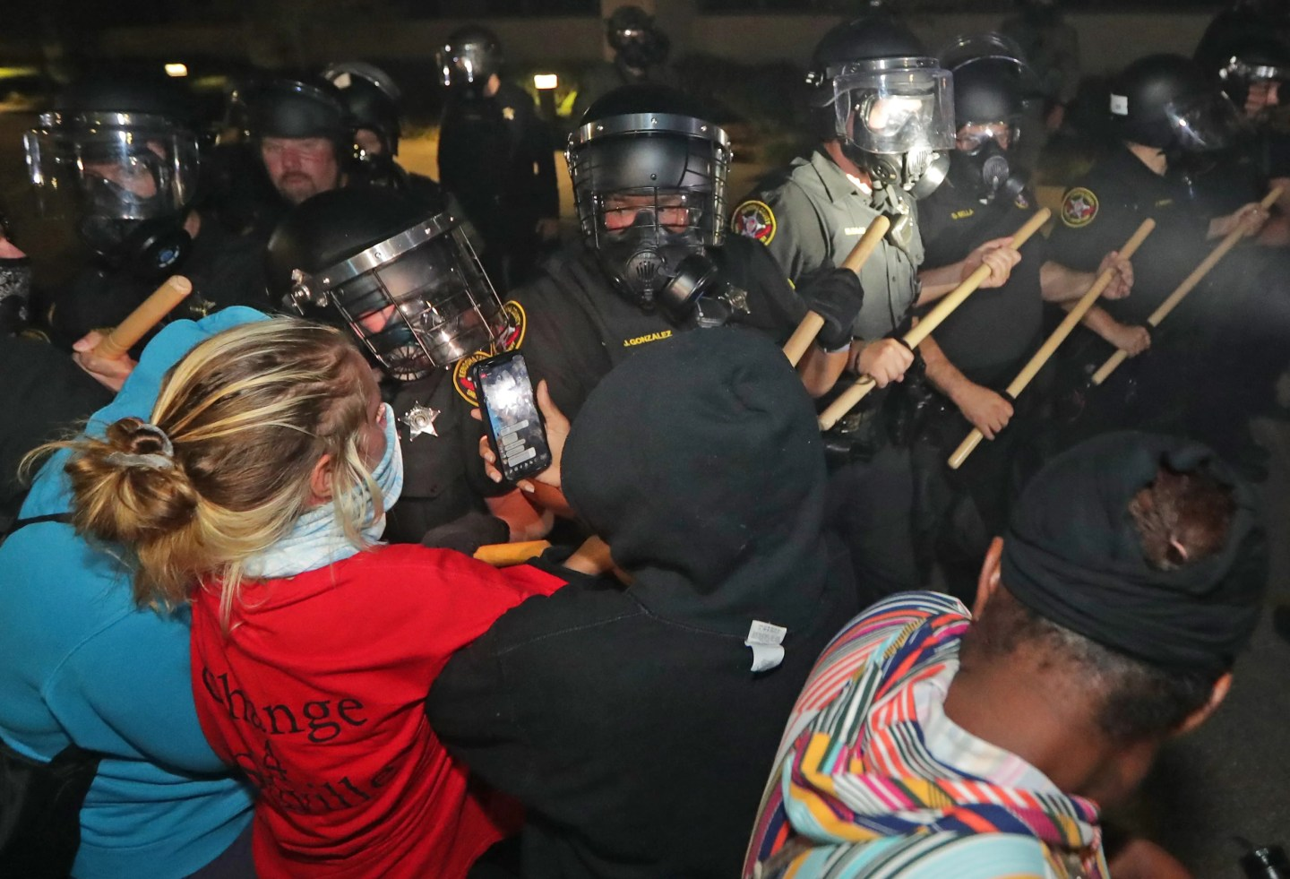 Police in riot gear confront protesters outside the police department in Kenosha, Wisconsin, on Sunday, Aug. 23, 2020. Kenosha police shot a man Sunday evening, setting off unrest in the city after a video appeared to show the officer firing several shots at close range into the man's back.