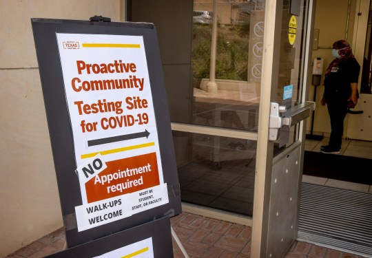 A sign directs people to a COVID-19 testing site at the Student Services Building on the University of Texas campus on Aug. 24. The university is encouraging students to get tested for coronavirus before they leave for Thanksgiving break.