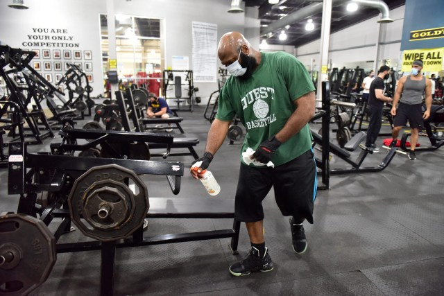 Burnell Franklin, of Paterson, wipes down his workout area at Gold's Gym, which reopened to the public after being closed since March due to the Covid-19 pandemic in Totowa, N.J. on Tuesday Sept. 1, 2020.